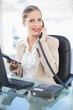 Smiling blonde businesswoman on the phone holding calculator