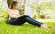 Happy young woman leaning against a tree while using her noteboo