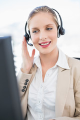 Content blonde call centre agent interacting with customer