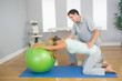 Physiotherapist controlling patient doing exercise with exercise
