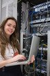 Woman happily using laptop to work on servers