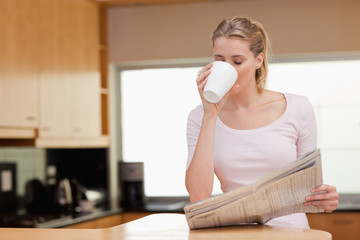 Woman reading the news while having coffee