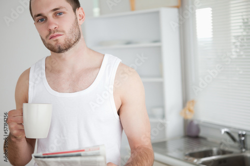 Healthy man drinking tea while reading the news