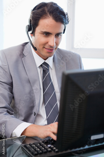 Portrait of a happy sales assistant working with a monitor
