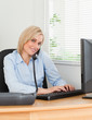 Smiling businesswoman on the phone while typing looks into camer