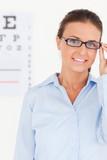 Portrait of a brunette eye specialist wearing glasses looking in