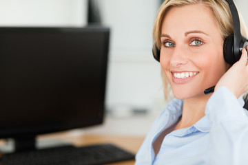 Portrait of a smiling blonde businesswoman with headset working
