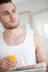 Portrait of a good looking man drinking orange juice while readi