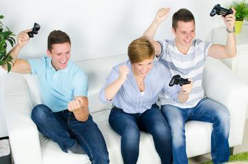 drei jugendliche jubeln beim spielen an der konsole