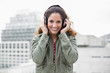 Cheery smiling gorgeous brunette in winter fashion listening to
