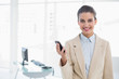 Content smart brown haired businesswoman holding a mobile phone