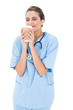 Peaceful brown haired nurse in blue scrubs enjoying coffee smell