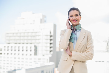 Happy smart brown haired businesswoman making a phone call