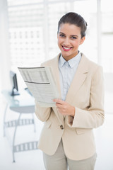 Content smart brown haired businesswoman reading a newspaper