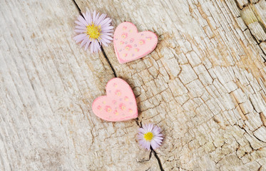 Two little pink hearts on wooden background