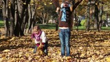 Two little girls throw fall leaves into air