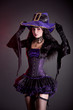 Smiling witch in purple and black gothic Halloween costume