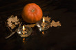pumpkin and two lighted candles on a dark background