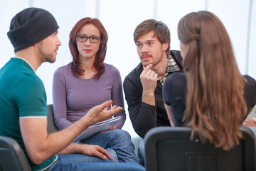 Group of people listening to what young man saying