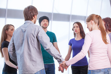 Group of people standing in circle.