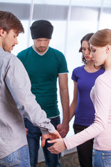 Close up of people holding hands. While standing in circle