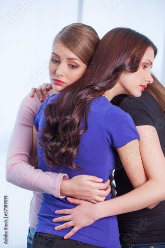 Three women hugging each other. Photo in halfbeak