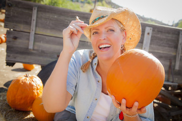 Beautiful Blond Female Rancher In a Cowboy Hat Holds a Pumpkin