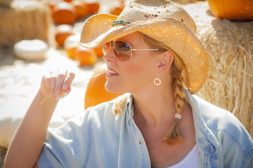 Beautiful Female Rancher Wearing Cowboy Hat in Pumpkin Patch