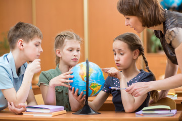 school kids studying a globe together with teacher
