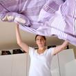Frau im Schlafzimmer macht Bett