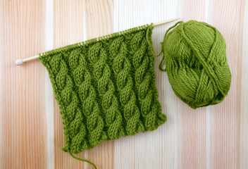 Green cable stitch knitting with a ball of yarn