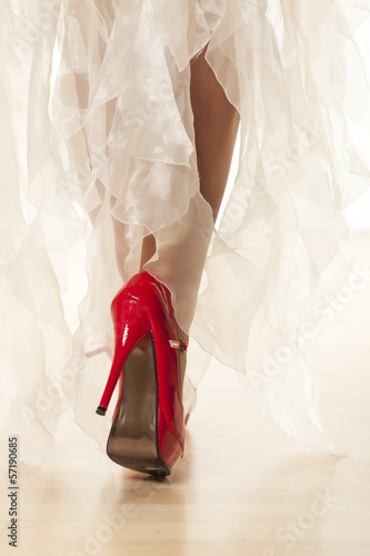 woman's leg in red high heels while walking