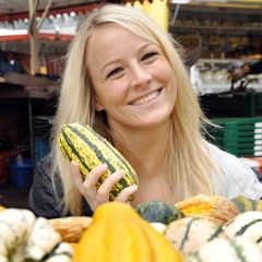 Frau kauft Kürbis auf Markt