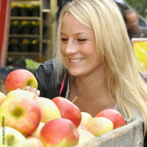Frau kauft Apfel auf Markt