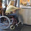 Frau im Rollstuhl vor defektem Lift
