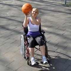 Frau im Rollstuhl spielt Basketball