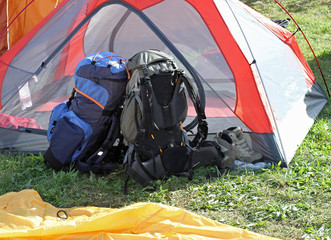 backpacks of hikers resting above the tent