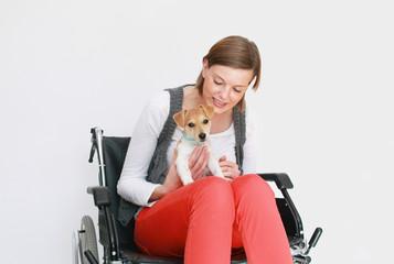 junge Frau im Rollstuhl mit Hund