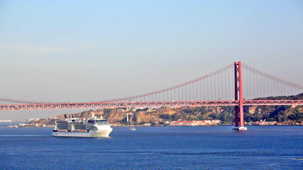 Big ship floats under the bridge on April 25 in Lisbon, Portugal
