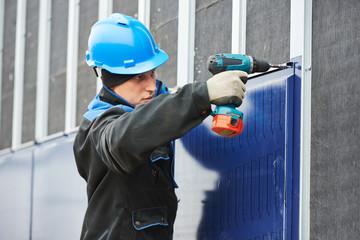 worker assembling facade metal construction