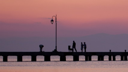 Family walking their dog on a pier at sunset