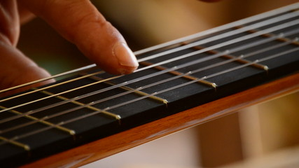 Luthier playing the strings of a guitar