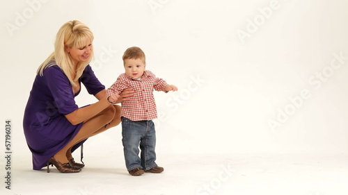 Little boy learning to walk with the help of his mother