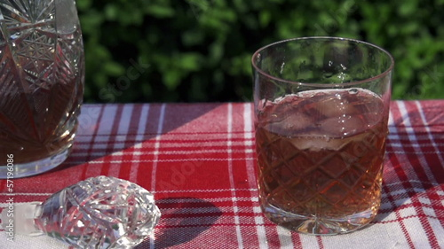 ice cubes throwing into the glass of whisky, slow motion shot at