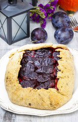 Plum galette on wooden table. Raw plums and pumpkins in the back