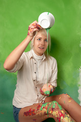 young woman pouring a green paint on herself from a cup