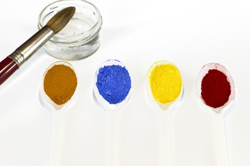Pigments powder with a bowl of water and a brush