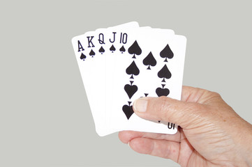 Isolated Hand Held Royal Flush Of Spades
