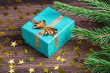 Christmas gift with stars and fir tree branch on wooden table