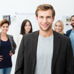 junger mann im büro mit team im hintergrund